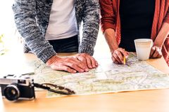 Senior couple with map at home, making plans. Royalty Free Stock Photos