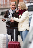 Senior couple with map and luggage. Cheerful elderly couple with luggage standing at street and checking direction Stock Photography