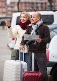 Senior couple with map and luggage Stock Images