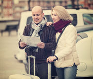 Senior couple with map and luggage. Mature couple with luggage standing at street and checking direction Royalty Free Stock Images