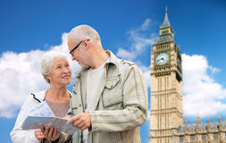 Senior couple with map over london big ben tower. Family, age, tourism, travel and people concept - senior couple with map over big ben tower in london city Royalty Free Stock Photos