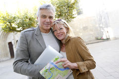 Senior couple with map and tablet outdoors Royalty Free Stock Photo