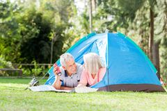 Senior Couple With Map And Torch In Tent Royalty Free Stock Images