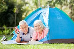 Senior Couple With Map And Torch In Tent Royalty Free Stock Photos