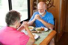 Senior Couple - Mealtime Prayer. Senior couple say a prayer of thanksgiving over a turkey dinner in their motor home Stock Image