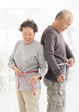 senior couple measuring  belly with measurement tape Stock Photos