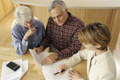 Senior couple meeting with agent. Mature couple talking to financial planner at home Stock Photos