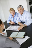 Senior couple meeting architect at office Stock Photography