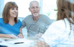 Senior couple meeting financial adviser; light effect. Senior couple meeting financial adviser for investment; light effect stock photo