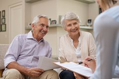 Senior couple meeting financial advisor. Senior couple meeting real estate agent at home. Old husband and wife with financial advisor for investment stock photography