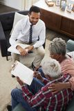 Senior Couple Meeting With Male Financial Advisor At Home And Signing Document stock image