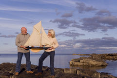 Senior couple with model boat on rocks by sea Royalty Free Stock Photo
