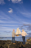 Senior couple with model boat on rocks by sea, rear view Royalty Free Stock Photos