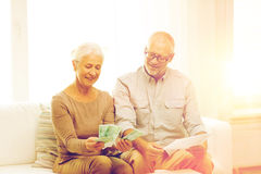 Senior couple with money and calculator at home Stock Photo