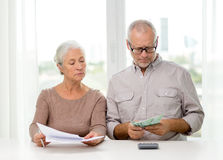 Senior couple with money and calculator at home Stock Photos
