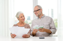 Senior couple with money and calculator at home. Family, savings, age and people concept - smiling senior couple with papers, money and calculator at home Royalty Free Stock Image