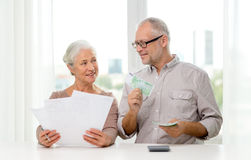 Senior couple with money and calculator at home. Family, savings, age and people concept - smiling senior couple with papers, money and calculator at home Stock Photo