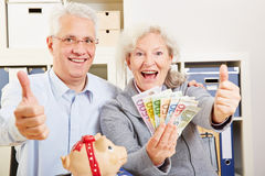 Senior couple with money holding Stock Photo