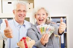 Senior couple with money holding Stock Photo