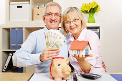 Senior couple with money and house and piggy bank Royalty Free Stock Photo