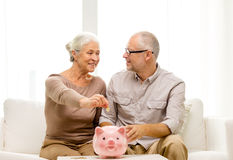 Senior couple with money and piggy bank at home Stock Image