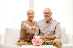 Senior couple with money and piggy bank at home. Family, savings, age and people concept - smiling senior couple with money and piggy bank at home Stock Images