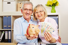 Senior couple with money and piggy bank. Smiling senior couple with euro money bills and a piggy bank Stock Photo