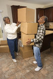 Senior Couple With Moving Boxes. Smiling senior african american man balancing moving boxes while his wife helps. Vertical shot Stock Photos
