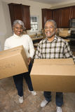 Senior Couple With Moving Boxes. Portrait of smiling senior african american man and woman with moving boxes in a new home.   Vertical shot Stock Photography