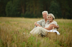 Senior couple on mowed field of wheat Stock Images