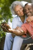 Senior couple with MP3 player, smiling royalty free stock photos