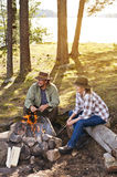 Senior couple near a lake sitting by a camp fire Royalty Free Stock Photography