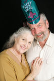 Senior Couple New Years Eve. Beautiful couple in their sixties posing for a romantic portrait on New Year's Eve.  Black background Stock Photography