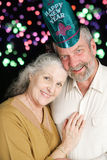 Senior Couple New Years Fireworks. Beautiful couple in their sixties posing for a romantic portrait on New Year's Eve.  Fireworks in the background Royalty Free Stock Image