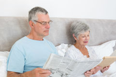 Senior couple with newspaper and book in house Stock Image
