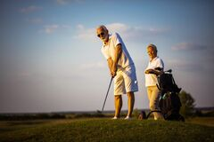 Free Senior Couple On Golf Court. Focus Is On Man. Stock Image - 218039881