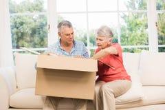 Senior couple opening big box Stock Photography