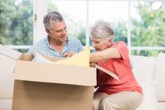 Senior couple opening big box Royalty Free Stock Image