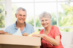 Senior couple opening big box. In living room Stock Photos