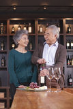 Senior Couple Opening Wine Bottle Stock Photography