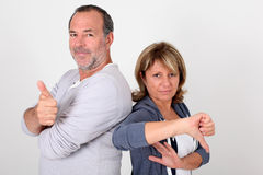 Senior couple with opposite expressions. Senior couple with thumbs up and down Royalty Free Stock Image