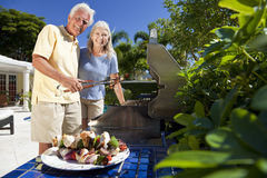 Senior Couple Outside Cooking Summer Barbecue. Happy senior men and women couple outside cooking kebabs on a summer barbecue royalty free stock photography