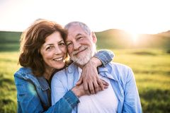 Senior couple outside in spring nature at sunset. Happy senior couple outside in spring nature at sunset royalty free stock image