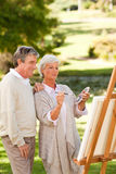 Senior couple painting in the park Royalty Free Stock Photos