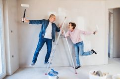 Senior couple painting walls in new home, having fun. Relocation concept. royalty free stock photography