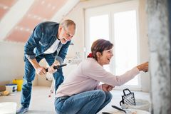 Senior couple painting walls in new home, relocation concept. stock images