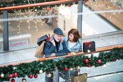 A senior couple with paper bags in shopping center at Christmas time. A high angle view of senior couple with paper bags in shopping center at Christmas time royalty free stock photo