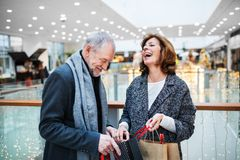 A senior couple with paper bags in shopping center at Christmas time. A senior couple with paper bags in shopping center at Christmas time, laughing stock photo