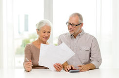 Senior couple with papers and calculator at home. Family, business, savings, age and people concept - smiling senior couple with papers and calculator at home Royalty Free Stock Photography