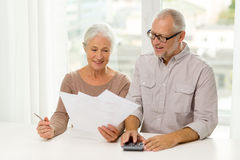 Senior couple with papers and calculator at home. Family, business, savings, age and people concept - smiling senior couple with papers and calculator at home Stock Photography